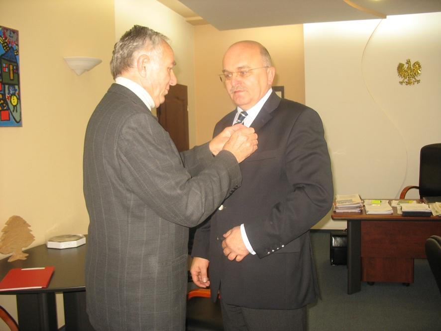 Ryszard Skorek przypina medal Staroście Józefowi Gismanowi